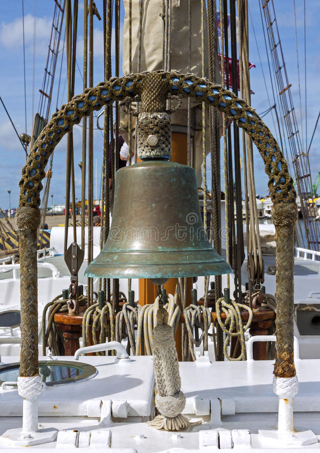Old ship deck with copper bell. Closeup of ship deck with sail ropes and old bell made of copper stock photos
