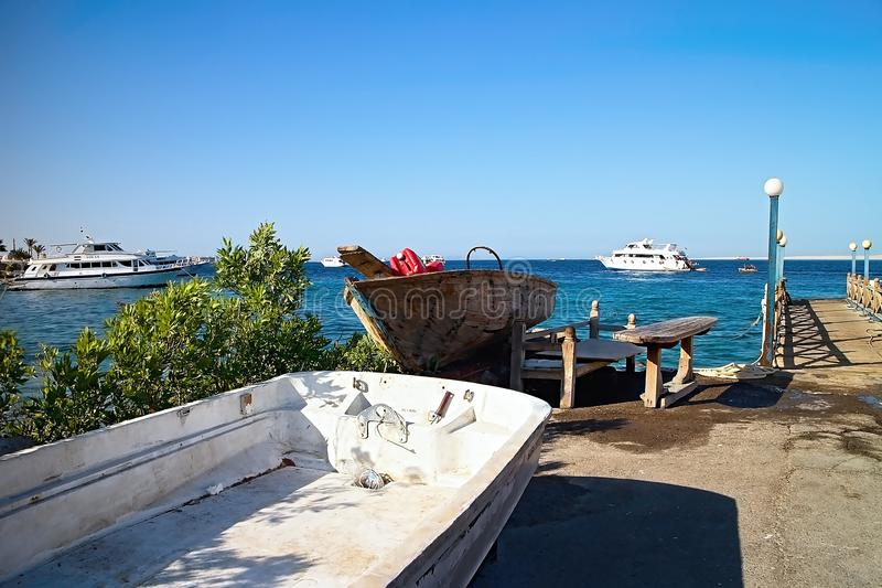 An old ship on the shore of the Red Sea in contrast to the backdrop of anchored modern ships. stock photography