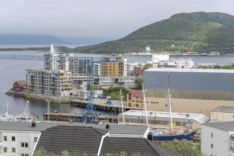 Old ships and new buildings at harbor, Harstad, Norway. HARSTAD, NORWAY - July 12 2019: Arctic circle fjord cityscape of little town harbor with new buildings stock image