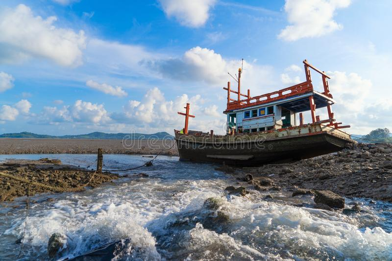An old shipwreck or abandoned fishing ship with waterfall and blue sky background in coast of Phuket City, Thailand. Seascape royalty free stock photo