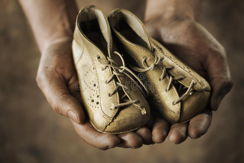 Old shoes. Dirty hands holding a pair of old childrens shoes royalty free stock photos