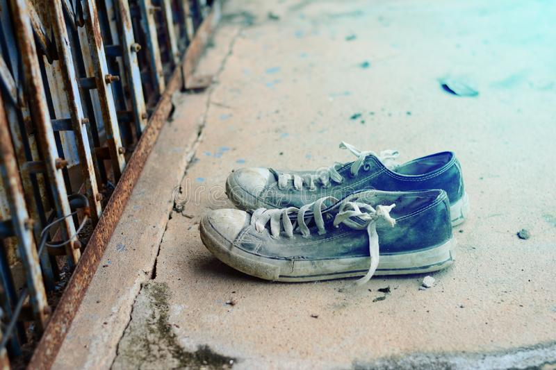 the old shoes in front of the metal slice door with dirty cemen royalty free stock photo