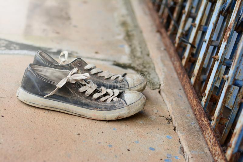 the old shoes in front of the metal slice door and dirty cemen royalty free stock image
