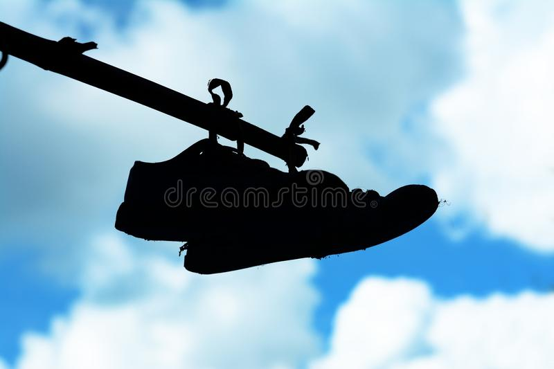 an old shoes hang on bamboo bar with blue sky and clouds royalty free stock image