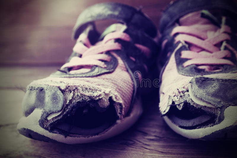 Old shoes with holes shoelaces worn shabby homeless clothing stock image