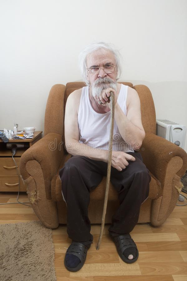 Old sick lonely man in the armchair at home stock photos