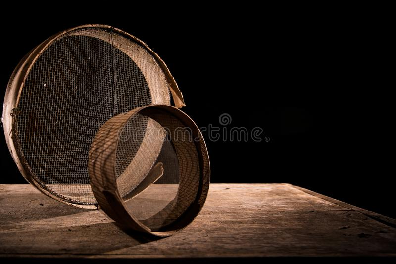Old sieves on a table. Two black antique sewing machines covered with dust on a wooden table with black background royalty free stock photos
