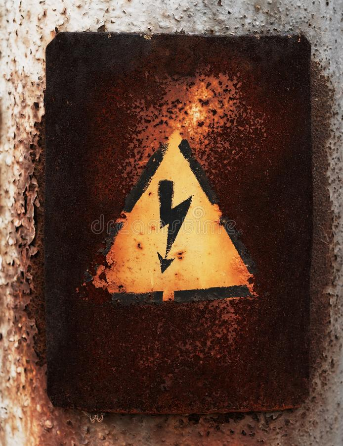 Old sign of danger of electric shock covered with rust.  royalty free stock photos