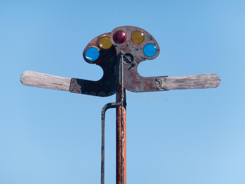 Old Signaler. Antique wood and metal railroad signaling device semaphore, with multi colored lenses and mechanical arms stock image