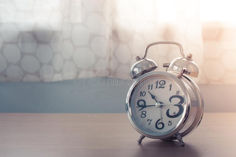 Old silver alarm clock on wooden table in bedroom with white curtain in the background. Selective focus stock image