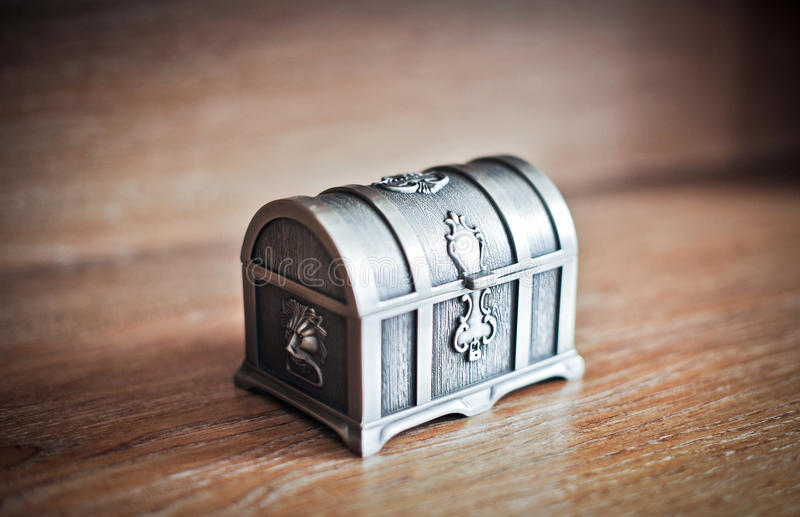 Old silver chest isolated on wooden table. Closed metallic retro casket. Jewelry vintage box stock image