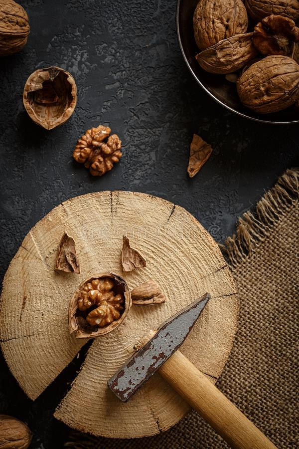 Old hammer and crushed walnut on dark background royalty free stock photo