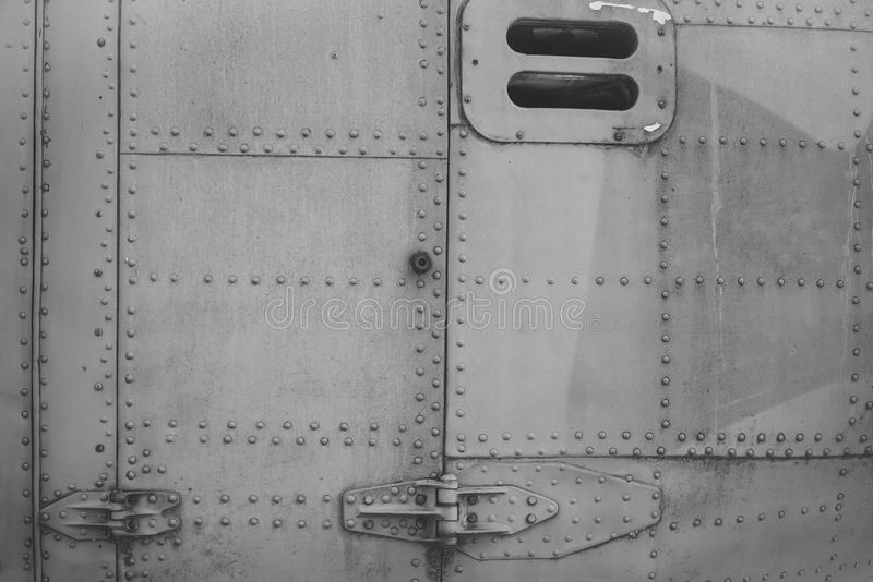 Old silver metal surface of the aircraft fuselage with rivets. Fuselage detail view. Airplane metallic fuselage detail royalty free stock photography