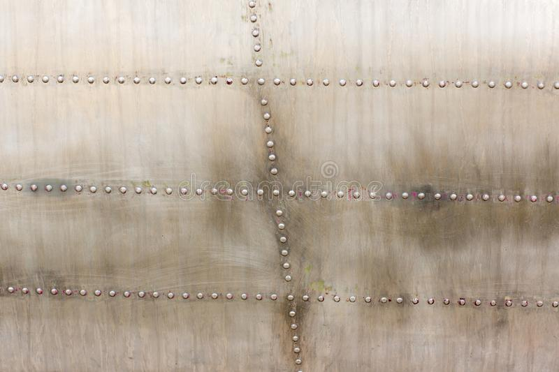Old silver metal surface of the aircraft fuselage with rivets. Iron plate,steel sheet texture,pattern and background. Aluminum surface of the aircraft fuselage stock photos