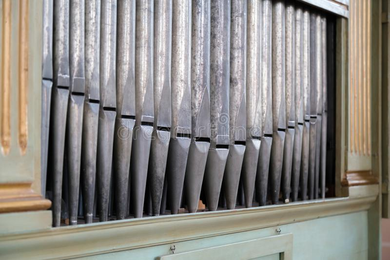 Old, silver organ pipes in a church used for playing sacred music. Many air pipes, sound tubes in the cathedral stock photography