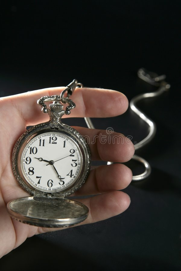 Old silver pocket watch clock on human hand stock photo
