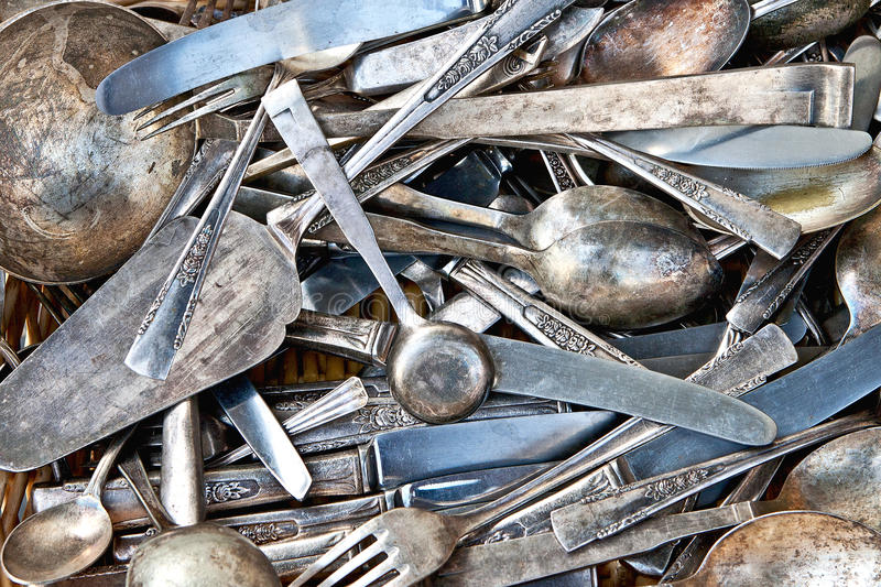 Old silverware. Background of vintage silverware: spoons, teaspoons, knifes, forks and other cutlery on a flea market table stock image