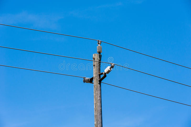 Old simple rural wood electrical pole on blue sky. Old simple rural weathered wooden utility pole with three parallel cables and insulators against blue sky stock images