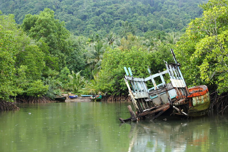 Old Sink fishing boat dock dead along mangrove canal river fores. Vintage Sink Boat and broken in Mangrove forest, rainy day stock image