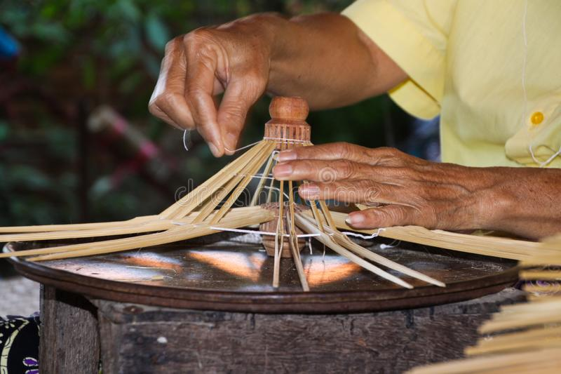 Old skinny hands producing frames for a paper umbrellas in Chiang Mai royalty free stock images