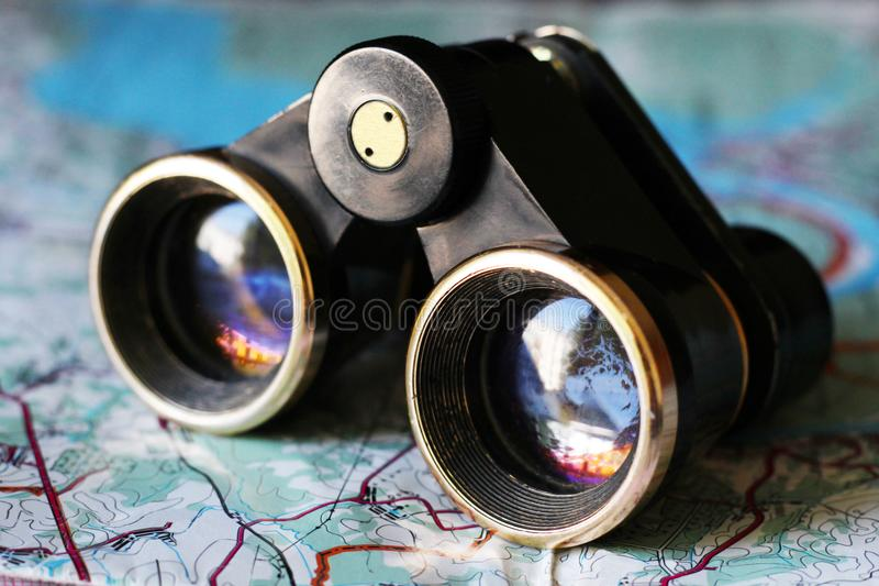 Old small binoculars on the map stock photos