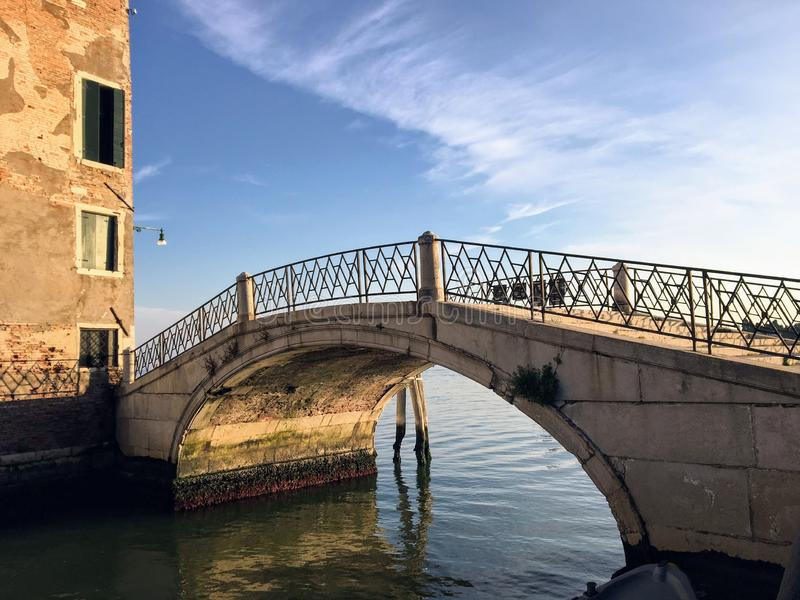 An old small historic stone bridge with iron railings crossing a canal with the open ocean in the background in Northern Venice. On a beautiful summer morning stock photos