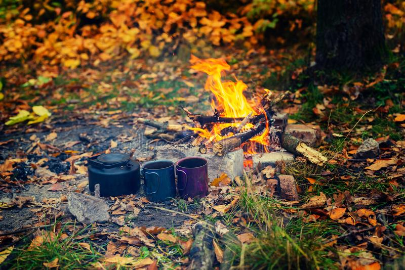 Old small kettle and mugs stand next to a bright bonfire royalty free stock photos