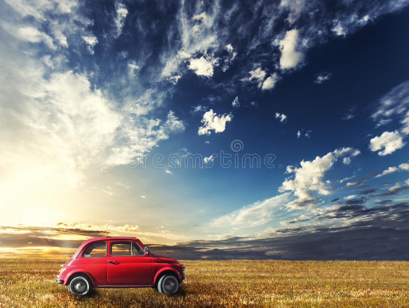 Old small red car Italian vintage. Natural landscape sunset. Old small red car Italian vintage. Natural landscape. A small red Italian car is parked in a country stock photos