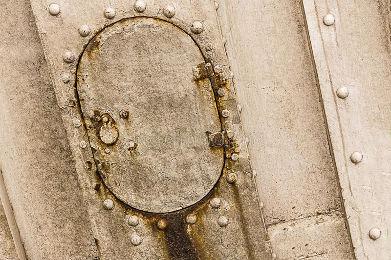 Old small rusty hatch oval door old boat weathered gray metal with lock rivets close-up background industrial stock photos