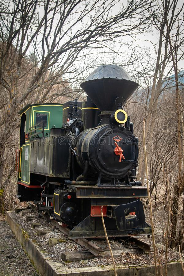 Old small steam locomotive on part of railway in the forest like a monument and tourist attraction stock images