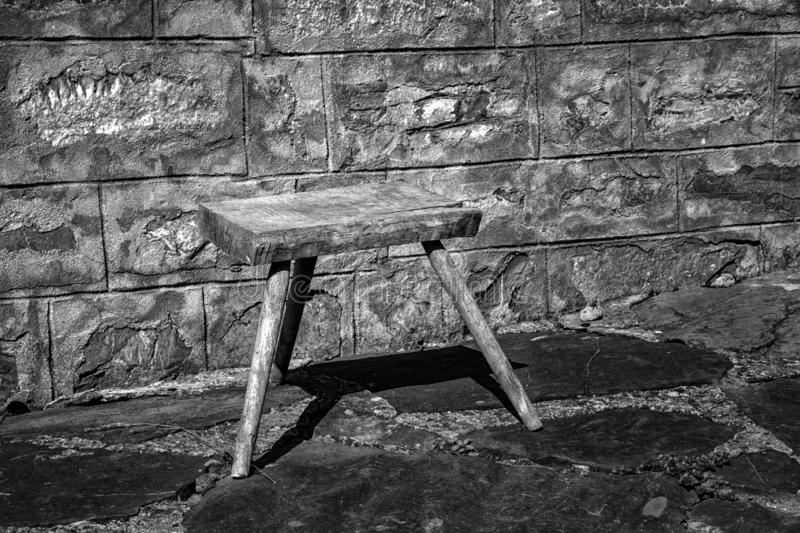 Old small wooden chair in the rural yard. Near a stone wall. Black and white royalty free stock images