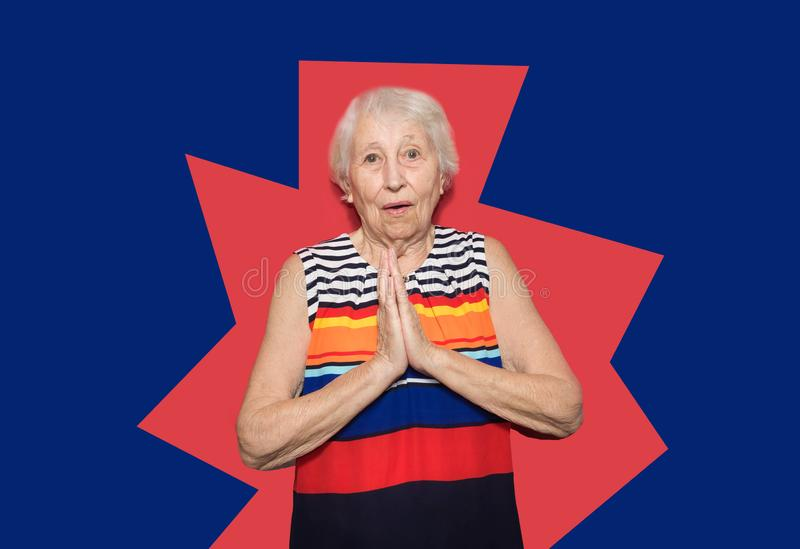 Old Woman with surprised expression on her face. Old smiling woman with surprised expression on her face on red studio background. Human emotions concept stock images