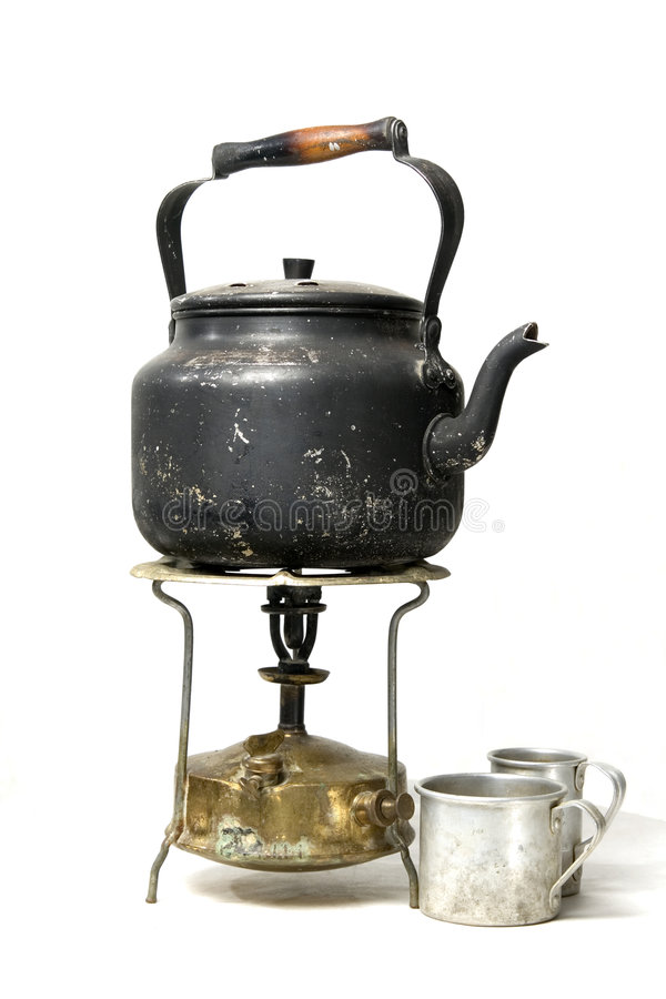 Old smoked teapot on a kerosene stove stock photos