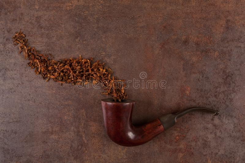 Old smoking pipe and tobacco on a vintage background. Above royalty free stock image