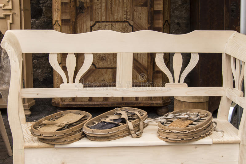 Old snowshoes seen on flea market. Wooden bench at Italian flea market with three pair of old snowshoes stock image