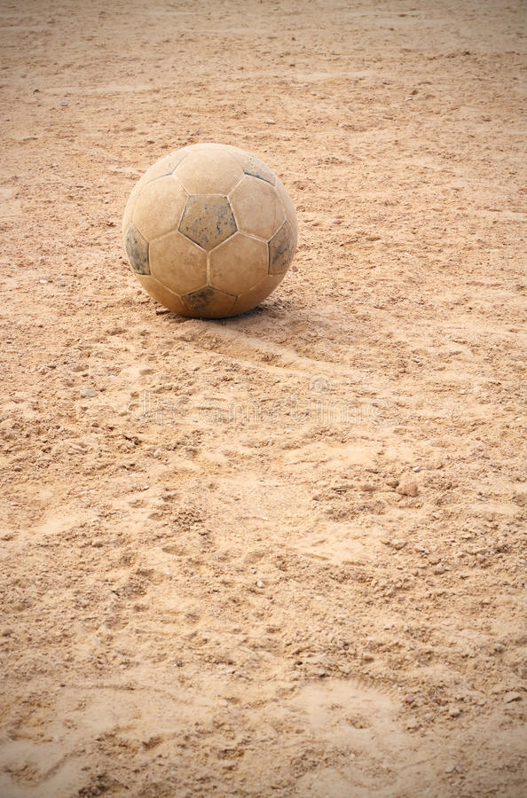Old soccer ball. On earth playground royalty free stock images
