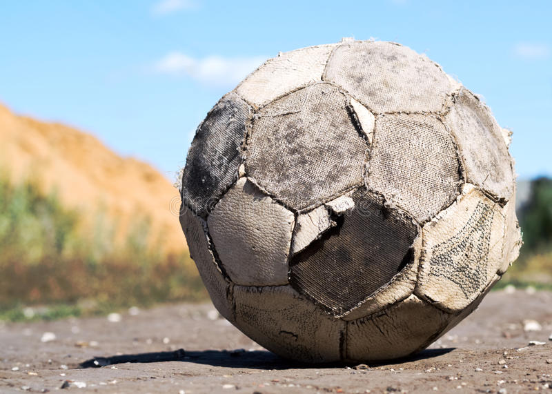 Old soccer ball. Old battered soccer ball on the road stock photos