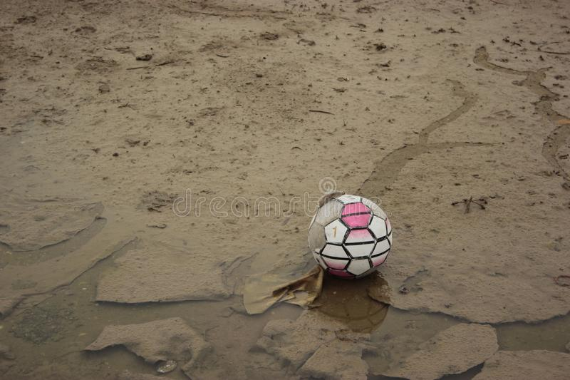 Old soccer ball staying on a mud ground. Photo of an old and dirty soccer ball staying on a mud ground royalty free stock photo
