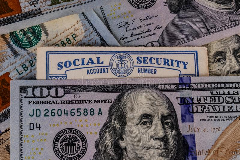 Old Social Security card and a bed of money representing the high cost of living on a fixed income III royalty free stock photo