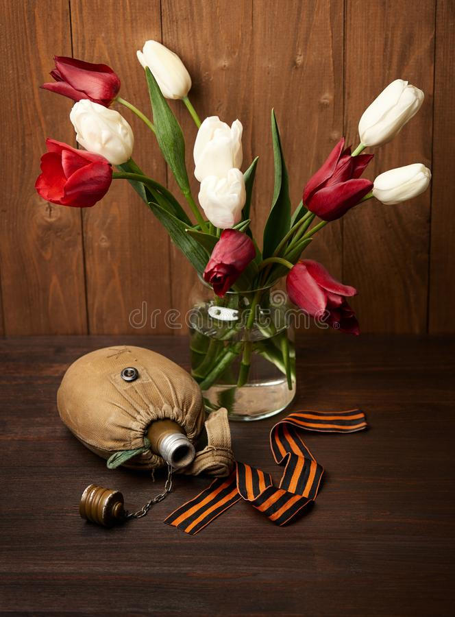 Old soldier`s flask and St. George`s ribbon on wooden background, world war II memorial concept and fallen warriors stock photo