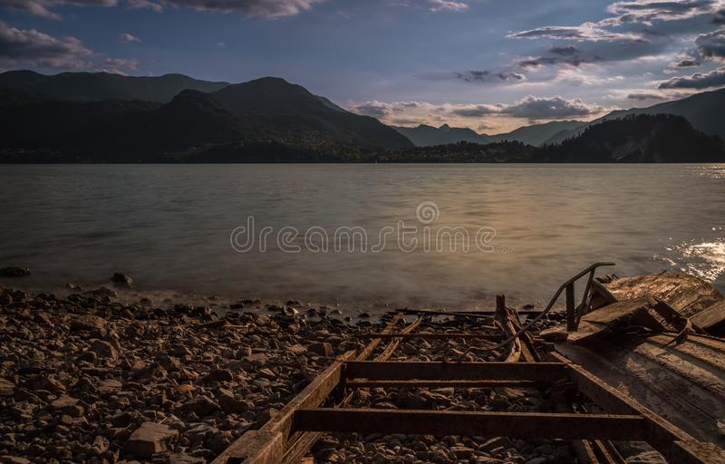 Old solitary boat wood destroyed aground in a lonely beach lake royalty free stock photography