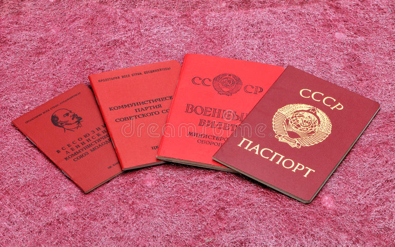 Old Soviet documents on a red background.  stock photos