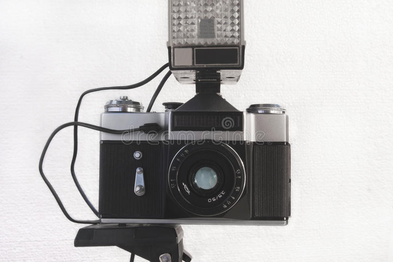 Old Soviet film camera on a tripod with a flash and a lens on a. White background royalty free stock image
