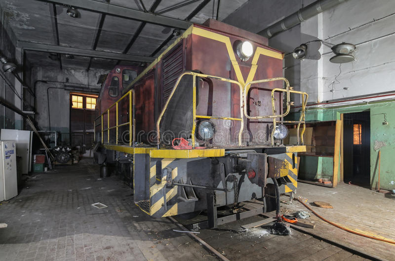 Old soviet shunting diesel locomotive in the abandoned room for servicing.  royalty free stock photography