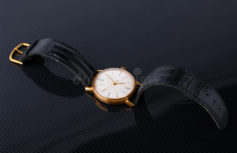 Old soviet wristwatch on black glossy background royalty free stock photos