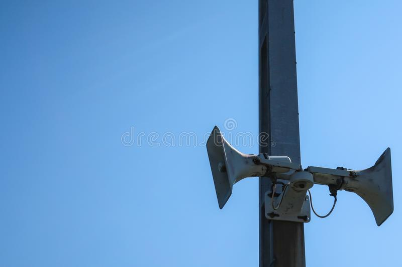 An old speaker / megaphone mounted on a post. Blank copy space for own text stock photos