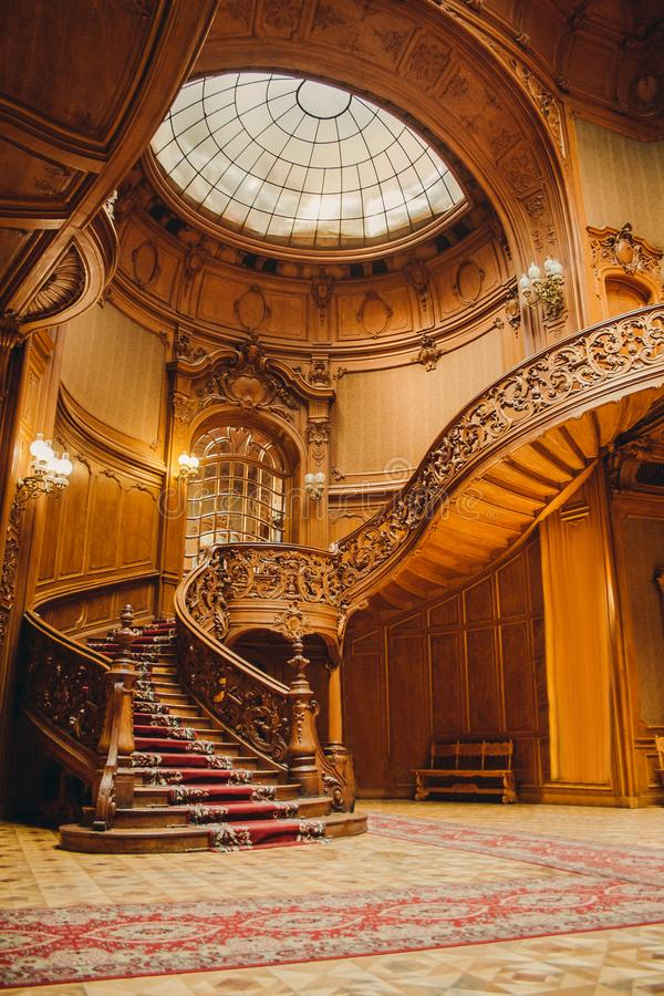 Old spiral wooden staircase with vintage railing indoors. luxury carved wood interior in the hall of an aristocratic palace. rare stock image