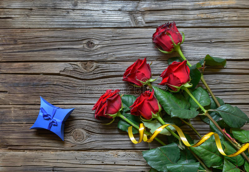 Old splintered wood background with stemmed roses. Old splintered wooden background under a bundle of five stemmed roses and star shaped blue box stock image