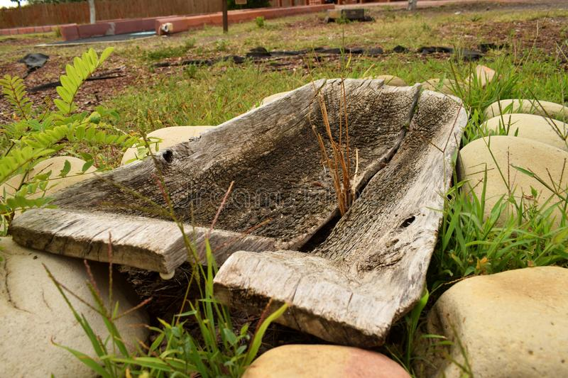Old split wooden trough. The old split wooden trough stands on round large smooth decorative stones. Bright green grass sucks through the stones royalty free stock images