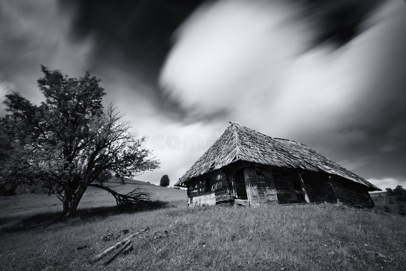 Old spooky abandoned farm house in black-white color. An old,long-abandoned house, against the background of a cloudy sky, shot on. A long exposure. Abandoned stock images